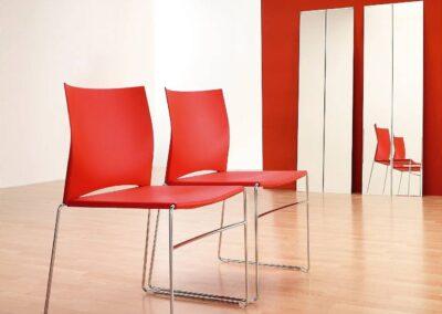 czerwone krzesła z metalowymi nogami